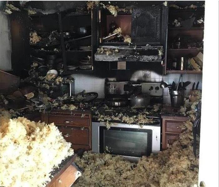 Fallen insulation and debris covering kitchen after a fire