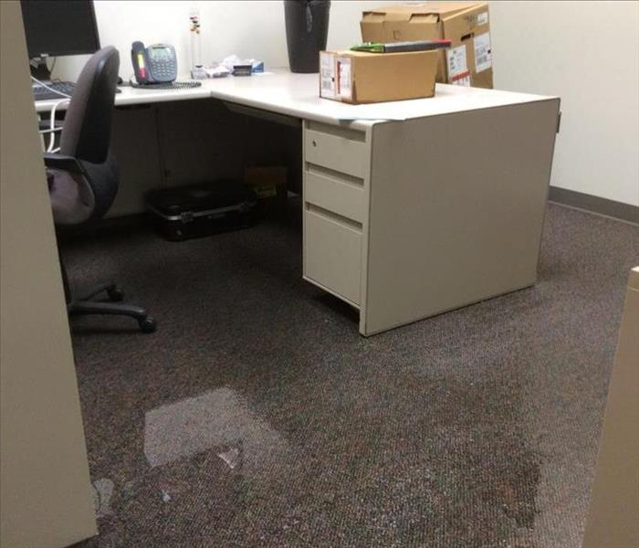 Blue carpet in office flooded with water