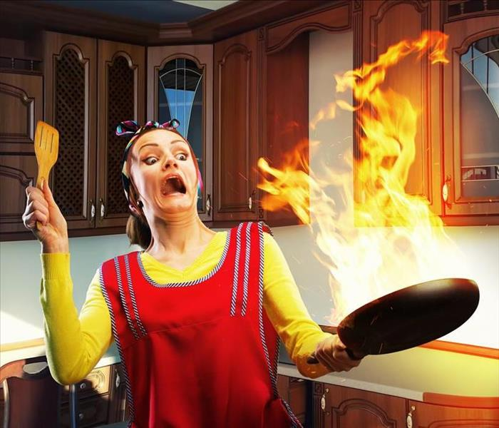 Image of woman in an apron holding a frying pan with fire.
