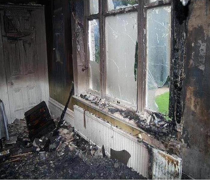 Window and wall of residential home damaged with fire, covered in soot and smoke.