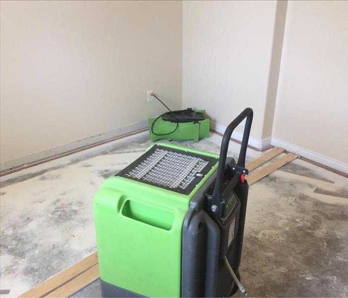Drying equipment placed in middle of bedroom with removed carpet.
